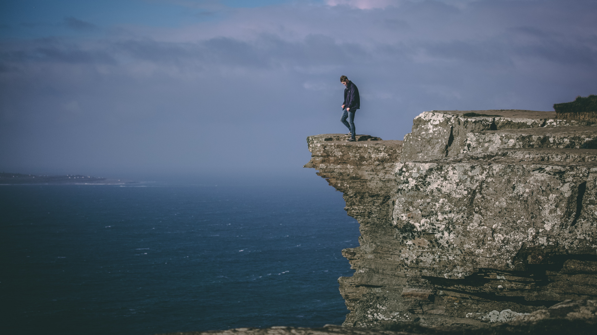 man-standing-on-cliff